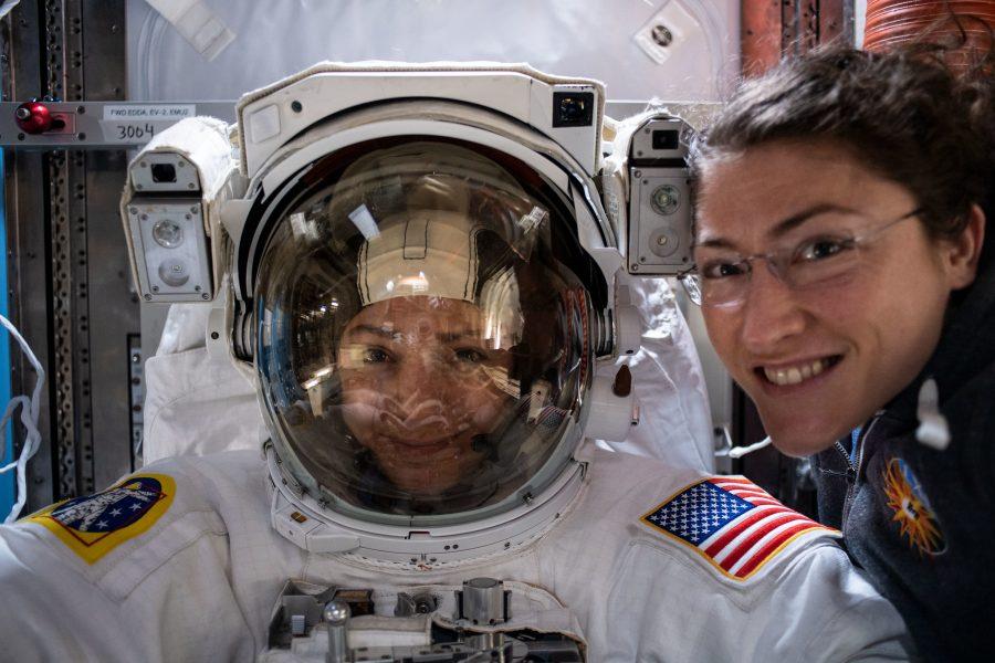 A astronauta da NASA, Christina Koch (à direita) posa para um retrato com a companheira de voo da Expedição 61, Jessica Meir, da NASA, que está dentro de um traje espacial dos EUA para uma verificação de ajuste.