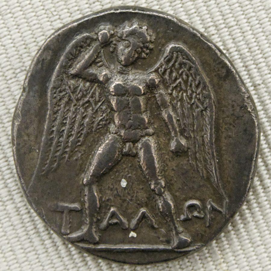 O gigante Talos representava como um jovem nu e alado, armado com uma pedra. Didracma de prata de Festos, Creta (c. 300 / 280-270 aC)