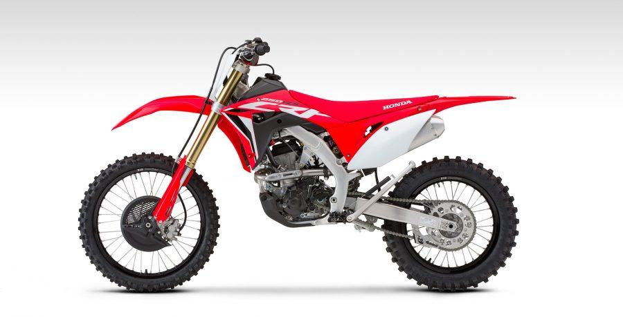 """Os grafismos injetados nos plásticos garantem mais durabilidade. Os aros, 21"""" na dianteira e 18"""" na traseira, são na cor preta, assim como o protetor de disco de freio dianteiro, proporcionando um visual de competição mais agressivo, inspirado nas motocicletas da HRC."""
