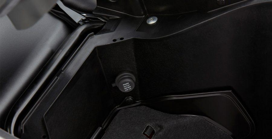 O porta-objetos tem iluminação interna de LED e uma tomada 12 V para carregar o seu smartphone.