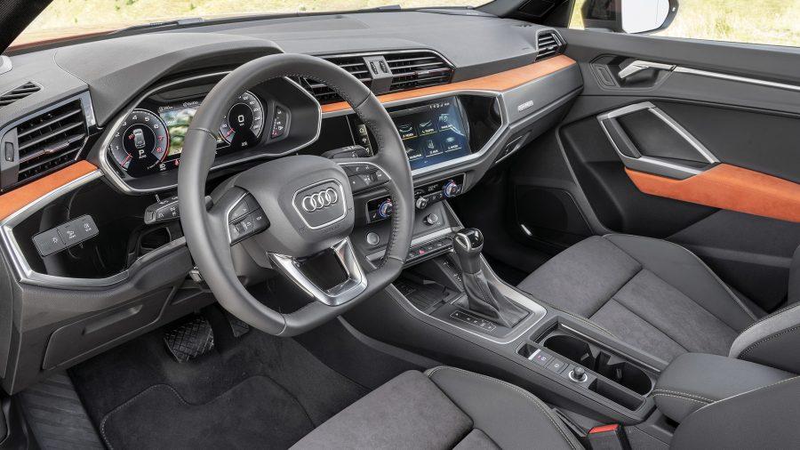 """O interior do novo Audi Q3 dá continuidade ao exterior do modelo. O painel, por exemplo, traz o desenho octogonal da grade Singleframe com seu visual na cor preta. O modelo também conta com controle por voz que compreende a linguagem cotidiana, Virtual Cockpit*, novo conceito do MMI com display de 8,8"""" sensível ao toque, quadro de instrumentos digital com uma tela de 10,25"""". Todos os displays, botões e controles estão ergonomicamente localizados. No escuro, o pacote de iluminação ambiente estabelece pontos de luminosidade no console central e nas portas. Ele pode ser configurado em 30 opções de cores e ilumina o compartimento embaixo do painel de instrumentos. Um modelo totalmente orientado ao motorista."""