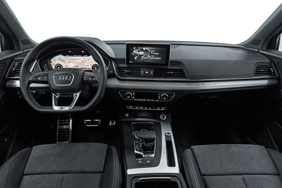 O interior em tons escuros possui costuras contrastantes no couro do volante e assentos esportivos revestidos de Alcantara, criando um ambiente dinâmico e elegante.